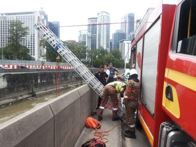 消拯员利用云梯与绳子,准备从大道下吊起尸体。