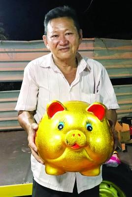 """林金福手拿""""金猪""""提早祝贺各界新年快乐。"""