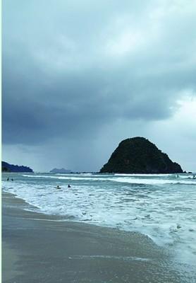 黑压压的乌云逼近,只有当地小孩依然敢浪涛间冲浪。