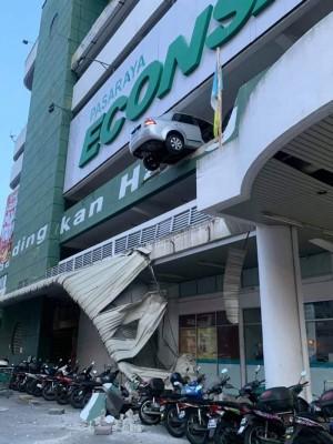 轿车撞破停车场2楼围墙。