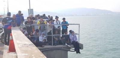 立在大桥路肩的记者们长时间顶着太阳曝晒守住现场。