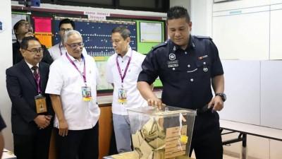 金马仑国席补选周二提早投票,警员准时到投票中心投下手中的一票。