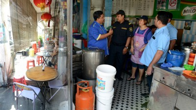 许多咖啡店为争取更大空间,将摊格和桌椅摆上五脚基。沙鲁丁(左1)和执法人员一起与小贩交涉沟通。