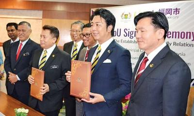 阿末法依沙(右3)见证阿都拉欣(左3)与高岛宗一郞(右2)交换签署谅解备忘录文件。