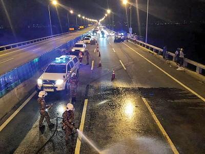 消拯员在事发后清洗桥上油迹,以避免大桥使用者发生意外事故。