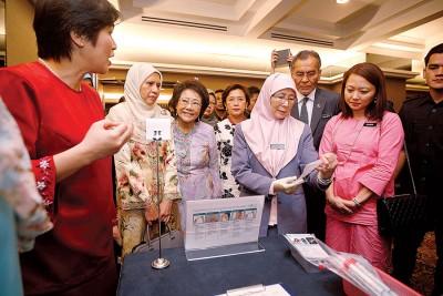 杨巧双(右起)、祖基菲里阿末及旺阿兹莎了解子宫颈抹片检验过程。