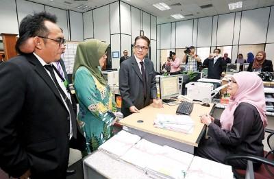刘伟强(左3)周一工作访问怡保联邦大厦内的法律援助局。