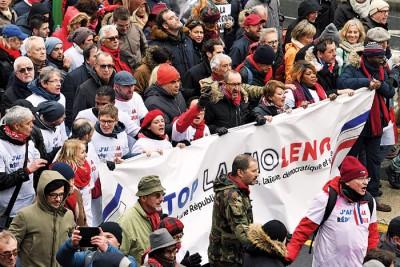 """大批民众披着红色围巾,周日在巴黎大街上游行,呼吁黄背心示威者""""维护民主""""。(法新社照片)"""