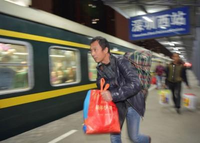 旅客近日拿着一袋二袋的行李赶上列车。