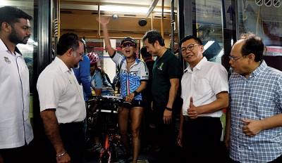 佳日星(左2)、尤端祥(右3)、郑来兴(右2)及安南(右)在光大巴士站迎接乘搭公交的折叠式脚踏车骑士。