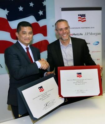 阿兹敏阿里(左起)和兰兹杜巴斯进行签署仪式,以见证马来西亚美国商会行政办公室开幕。