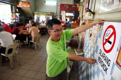 亚依淡滨滨茶室业者黄志彬一边张贴禁烟告示牌,一边提醒烟客到外边抽烟。