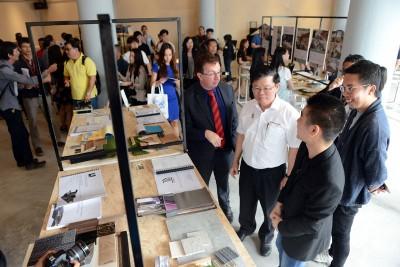 曹观友(中)在布莱恩查尔斯(左)的陪同下走访伯乐大学学院艺术院室内设计系毕业生的毕展。