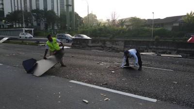 交警协助大道工作人员,捡起掉落在路面的三夹板木板与碎片。