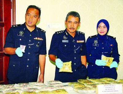 警方侦破美农毒品转运站,起获27公斤重海洛因及冰毒,阿兹里在沙萨里(左)及苏丽达陪同下,出示起获毒品。