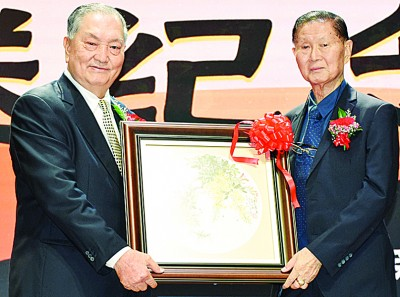 郑奕南(左)赠送日新独中美术主任陈玉凤老师画作给陈文彬。