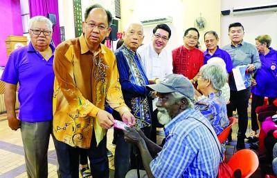 许综文(左2起)、顾承华、杨慕材、郑荣兴、陈树安及王益辉在理事陪同下,颁发红包予长者。