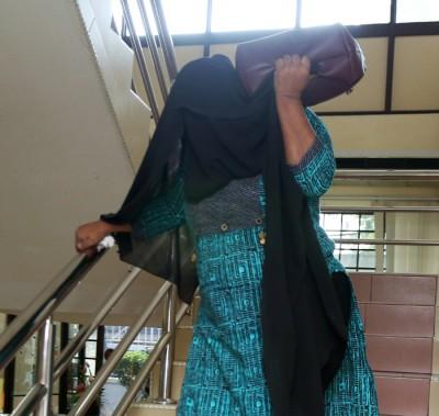 被控138项失信罪的巴杜玛德薇因用围巾遮头,致下楼梯时举步难行。
