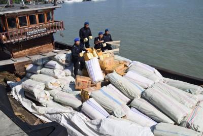 迪敏(右2)与水警们站在船上,出示起获的卷烟纸。