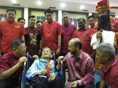 慕克里(右)派红包给陈淑群后,了解其情况,左为陈国耀。