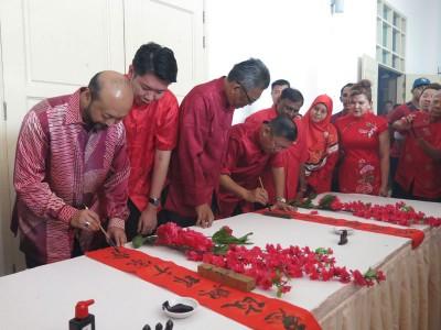 慕克里(左1)与陈国耀(左4)在孟达仑大臣官邸举行的新春活动上为春联填上一笔,左2及左3为黄思敏与依斯迈沙烈。