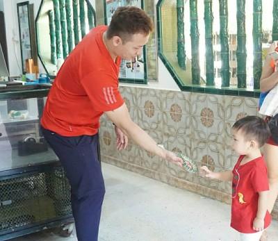 人小胆大,小孩子也敢伸手触摸蛇。