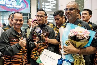 莫哈末里祖安(左2)返抵大马机场时受到接机欢迎,国家体理会副总监苏哈迪(左)亲自迎接莫哈末里祖安及其教练R贾格纳丹(右)。