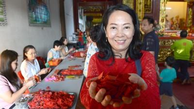 """谢亿莲用传统办法即为红纸包扎钱币,耗时3只周末,制造多达1万1000封红包来""""尚库""""。"""