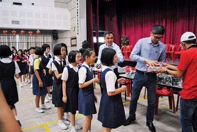 孙意志及邝志祥赠送小礼物予出席参与阅报计划的学生。