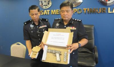 浮动再玛尼(右)亮警方起获的手枪及一枚在子弹。
