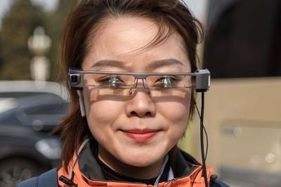 """河北一名女记者戴着""""第一视角直播眼镜""""颇为吸引眼球。该名女记者介绍,眼镜镜框上安有摄像头,能以第一视角向网民直播,""""我看见什么,网民就看见什么""""。(法新社照片)"""
