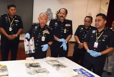 诺阿占手持疑犯贩毒方式的图片,对记者讲解。